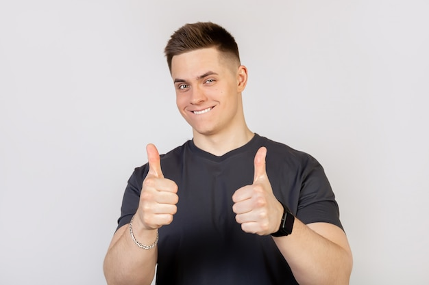Un giovane uomo su uno sfondo bianco, mostrando un dito fino alla telecamera con un sorriso felice.