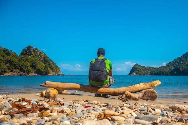 Un giovane uomo sulla spiaggia di puerto caribe seduto a punta de sal nel mar dei caraibi