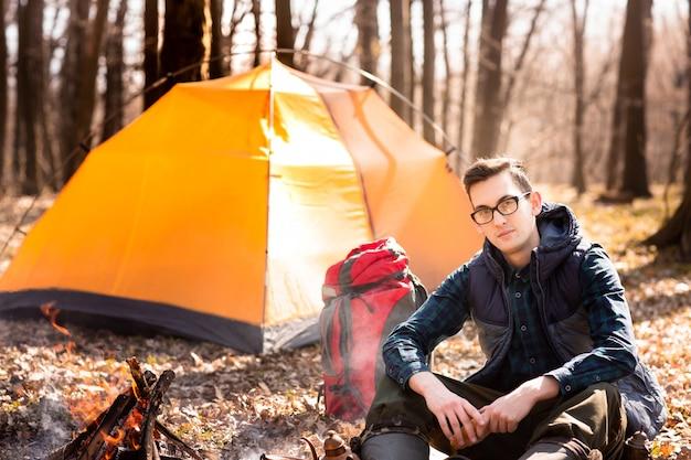 Un giovane viaggiatore nella foresta sta riposando vicino alla tenda e ha cucinato la colazione nella natura