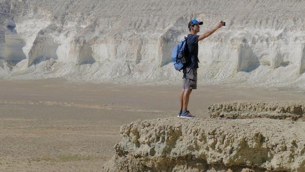 Un giovane viaggiatore si trova sul bordo di una scogliera e fa un selfie