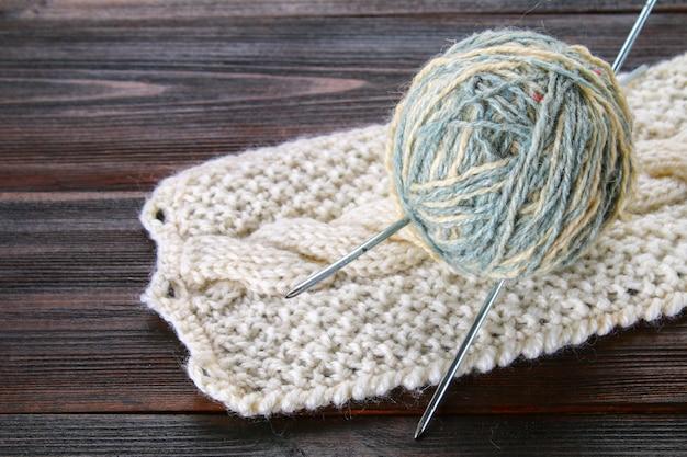 Un gomitolo di lana con ferri da maglia e calzini lavorati a maglia su un tavolo di legno. cucito