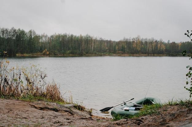 Un gommone, con scatole con attrezzi da pesca, nello stagno, lago. sfondo di pesca.