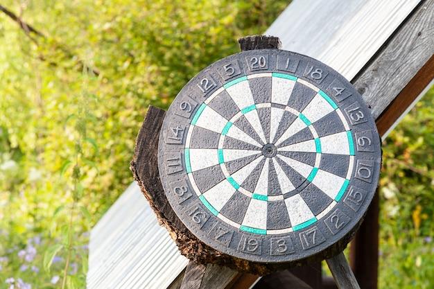 Un grande cerchio nero di freccette su uno sfondo di erba verde in una calda giornata estiva