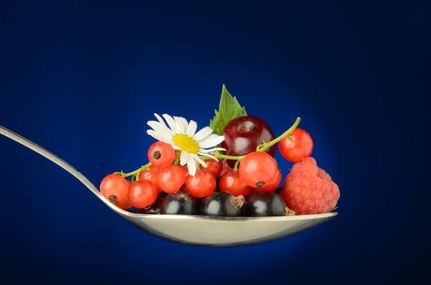 Un grande cucchiaio pieno di succose bacche selvatiche di ribes, ciliegia, lampone, ribes e ombretto, con foglie verdi e un fiore di camomilla su un blu. freschezza ed estate in un cucchiaio.