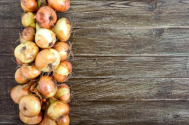 Un grande mazzo di cipolle su un tavolo di legno