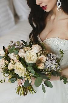 Un grande mazzo di fiori nelle mani della bellissima modella bruna dai grossi seni con grandi orecchini di lusso con diamanti nell'abito da sposa alla moda
