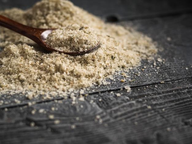 Un grande mucchio di sale con erbe con un cucchiaio di legno su un tavolo nero vintage.