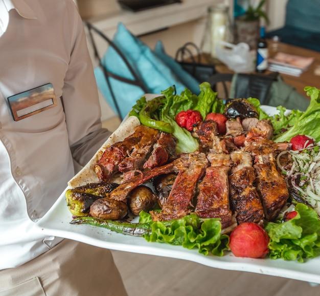 Un grande piatto bianco di varietà di kebab