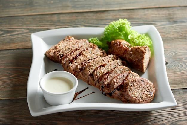 Un grande piatto bianco, servito con deliziose fette di carne ripiene con salsa all'aglio e decorato con foglie di insalata. buon antipasto per la cena al ristorante con vino rosso.