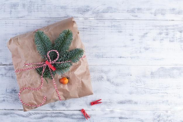 Un grande regalo in carta grigia legato con una corda, su un blu di legno