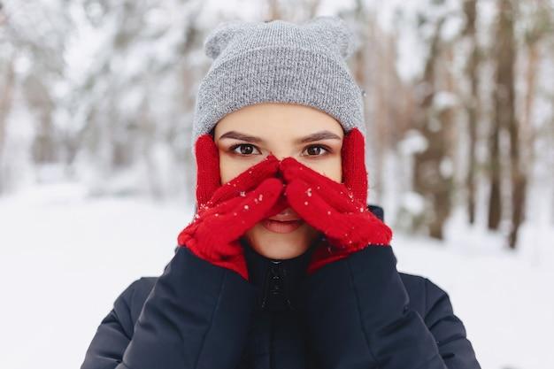 Un grande ritratto di una ragazza in guanti rossi con gli occhi espressivi in inverno