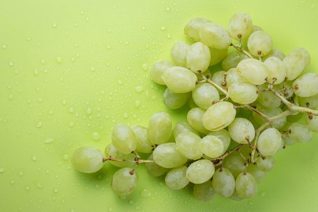 Un grappolo d'uva matura con gocce d'acqua, bacche di uva bianca