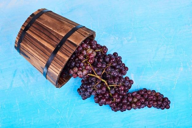 Un grappolo d'uva rossa da un secchio di legno su blu, vista dall'alto.