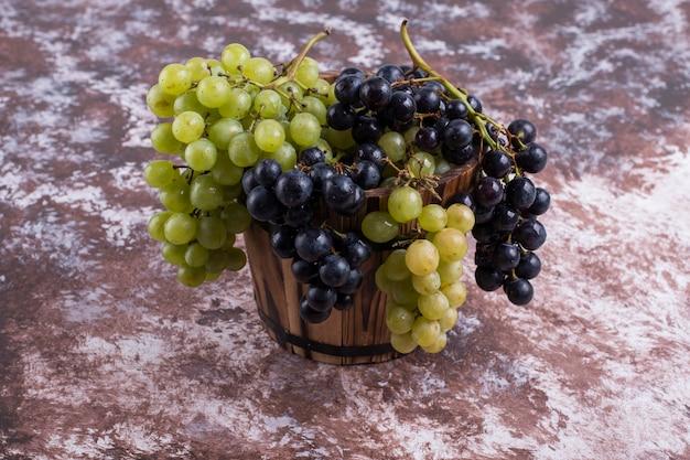 Un grappolo d'uva verde e rossa in un secchio di legno