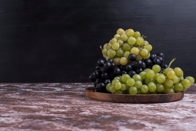 Un grappolo di uva verde e rossa in un piatto di legno su sfondo nero
