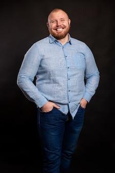 Un grasso uomo dai capelli rossi con la barba in camicia blu e jeans è in piedi con le mani in tasca e il sorriso