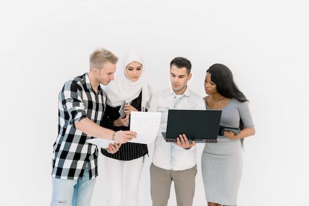 Un gruppo casuale felice di quattro persone multietniche che controllano il fondo bianco