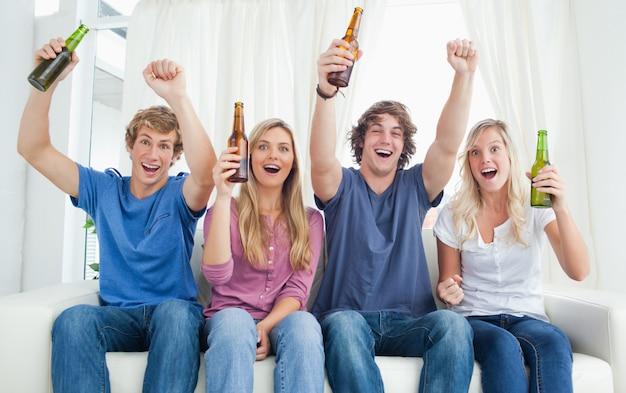 Un gruppo che celebra mentre guarda la macchina da presa con la birra in mano