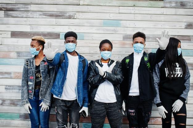 Un gruppo di amici adolescenti africani che indossano maschere mediche proteggono da infezioni e malattie da quarantena del virus coronavirus.