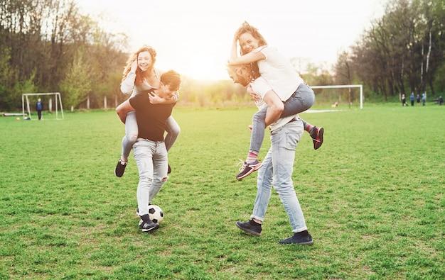 Un gruppo di amici in abito casual gioca a calcio all'aria aperta. le persone si divertono e si divertono. riposo attivo e tramonto scenico.