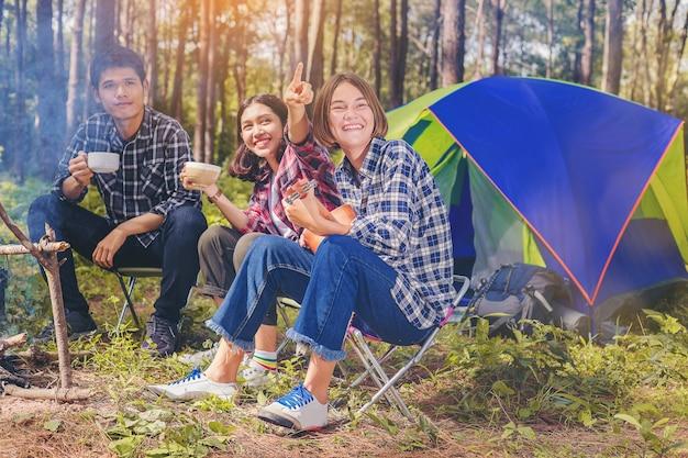 Un gruppo di amici si diverte con una bevanda calda e suona l'ukulele accanto alla tenda.