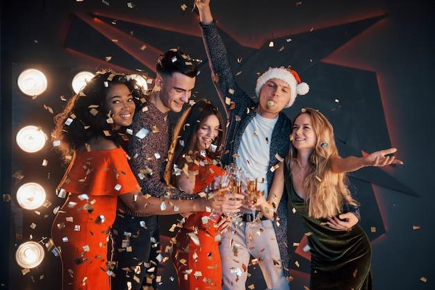 Un gruppo di amici si sta divertendo in bellissimi abiti in chiffon con champagne e coriandoli, in preparazione per il nuovo anno