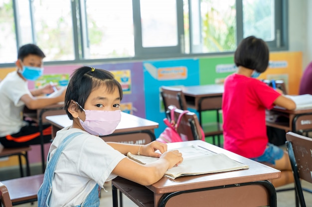 Un gruppo di bambini asiatici che indossano una maschera protettiva per proteggere da covid-19 seduto alla scrivania in aula, scuola elementare, distanza sociale, coronavirus si è trasformato in un'emergenza globale.