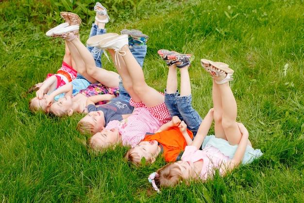 Un gruppo di bambini che giocano e corrono nel parco su un gozon verde.
