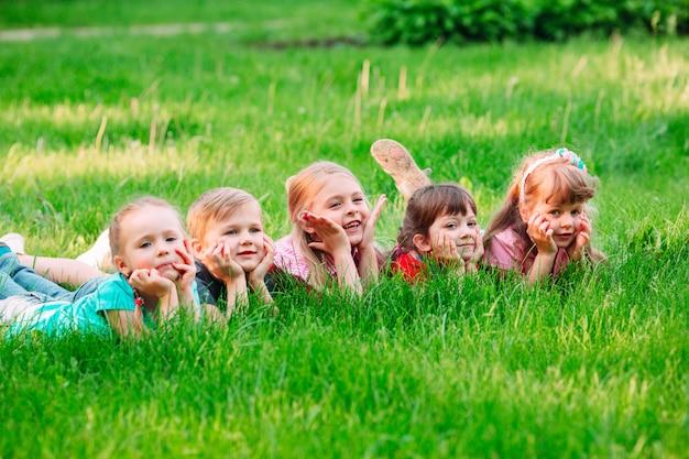 Un gruppo di bambini che si trovano sull'erba verde nel parco. l'interazione dei bambini.
