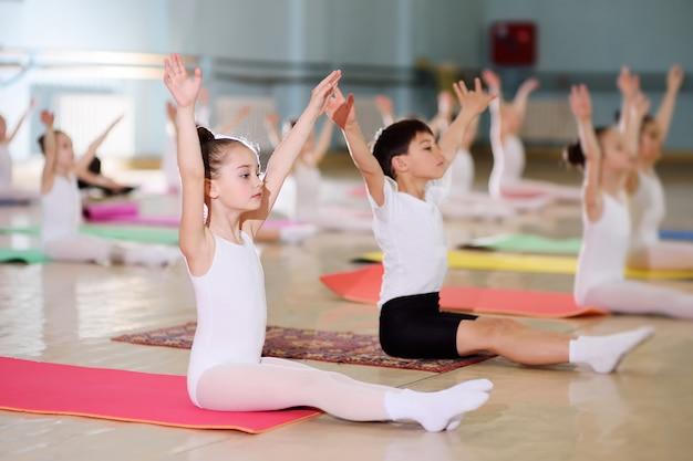 Un gruppo di bambini in una scuola di balletto o in una sezione di ginnastica sul carimatico