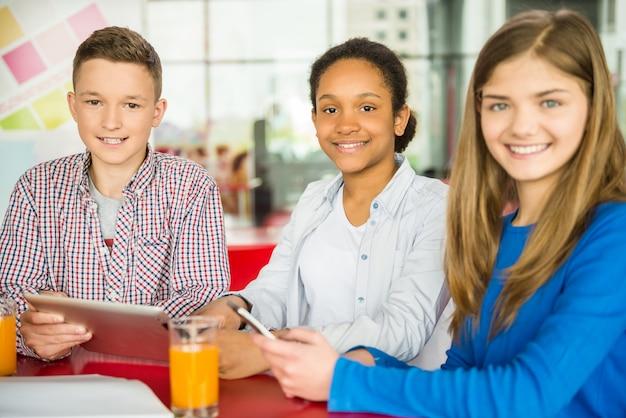 Un gruppo di bambini studia e beve succo d'arancia.