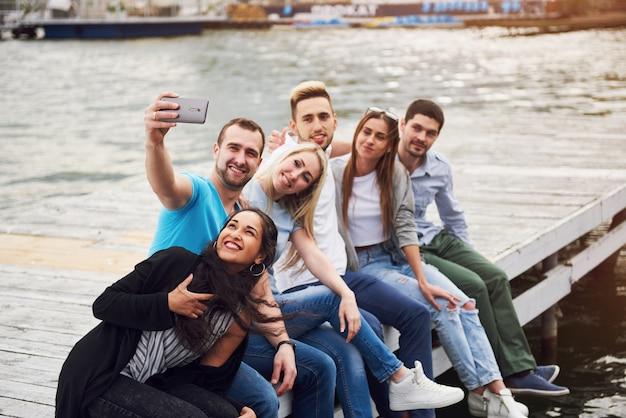 Un gruppo di bei giovani che fanno selfie sdraiati sul molo, i migliori amici di ragazze e ragazzi con il concetto di piacere crea la vita emotiva delle persone.