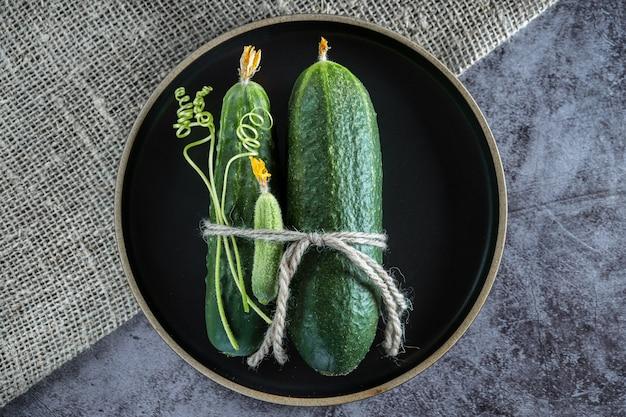 Un gruppo di cetrioli sul tavolo con indrigentov per la salatura: aglio, aneto. sfondo scuro