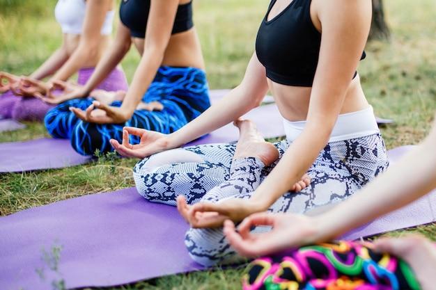Un gruppo di donne che fanno yoga sull'erba verde fresca all'aperto. uno stile di vita sano.