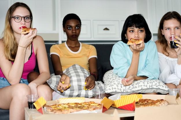 Un gruppo di donne diverse seduti sul divano e mangiando pizza insieme