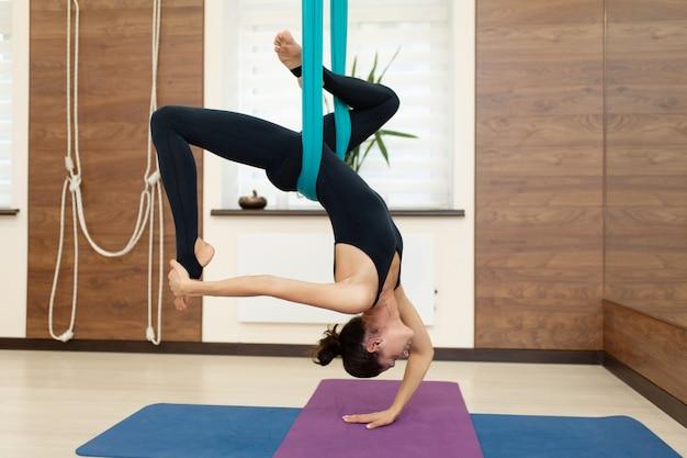 Un gruppo di donne è appeso a testa in giù su un'amaca. volare lezione di yoga in palestra. stile di vita in forma e benessere