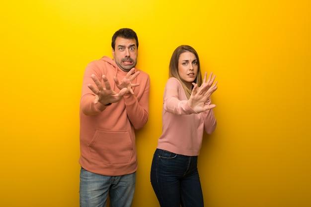 Un gruppo di due persone su uno sfondo giallo è un po 'nervoso e spaventato
