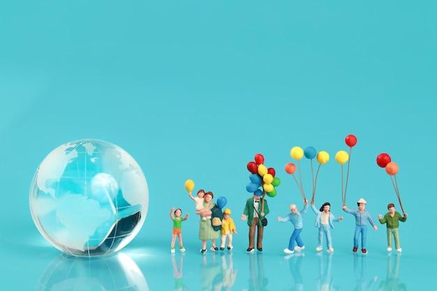 Un gruppo di famiglia felice si diverte e tiene in mano un palloncino con la terra