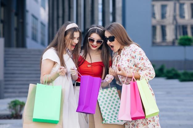 Un gruppo di giovane donna carina felice in abiti casual, top e pantaloni che camminano dall'edificio con borse gialle, verdi, viola e rosa nelle loro mani. giornata di sole, acquisti di successo. trucco casual.
