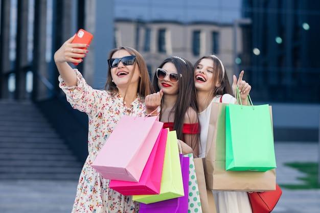 Un gruppo di giovani belle ragazze in abiti casual con occhiali da sole, trucco, cerchio per capelli e borse della spesa colorate che fanno selfie dopo lo shopping di successo