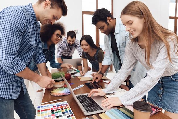 Un gruppo di giovani designer lavora insieme in un ufficio leggero.