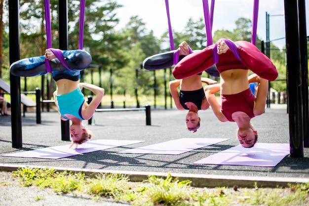 Un gruppo di giovani donne che fanno pratica di yoga aerea in amaca viola all'aperto
