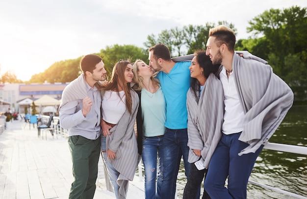 Un gruppo di giovani e di successo in vacanza al molo al sole.
