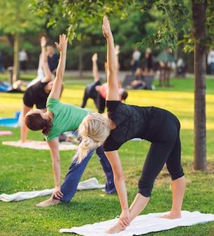 Un gruppo di giovani fa yoga nel parco al tramonto.