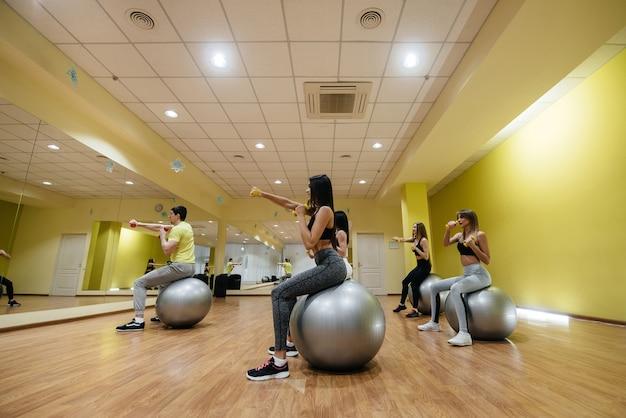 Un gruppo di giovani ragazze atletiche si esercita in palestra sotto la guida di un allenatore. uno stile di vita sano.