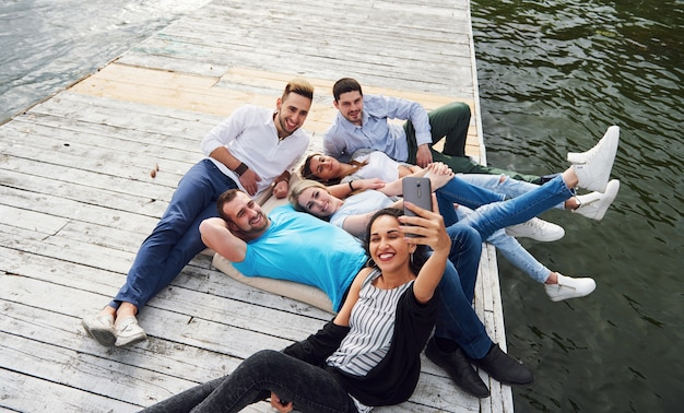 Un gruppo di giovani seduti sul bordo del molo e fanno selfie. amici che godono di una partita sul lago.