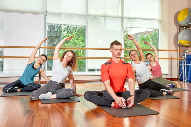 Un gruppo di giovani sportivi in abbigliamento sportivo, in una sala fitness, facendo flessioni o assi in palestra. concetto di fitness di gruppo, allenamenti di gruppo, motivazione