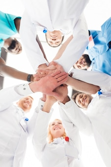 Un gruppo di medici si tengono per mano.