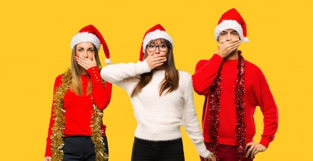 Un gruppo di persone donna bionda vestita per le vacanze di natale che copre la bocca