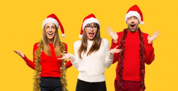 Un gruppo di persone donna bionda vestita per le vacanze di natale con espressione sorpresa
